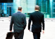 Businessmen walking towards building, rear view, blurred