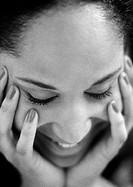 Woman holding face with hands, eyes closed, close-up, B&W