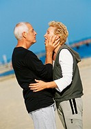 Mature couple standing on beach, embracing, side view