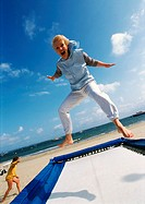 Mature woman jumping on trampoline at the beach