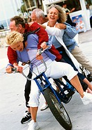 Mature men and women on tandem bike, falling to side, portrait
