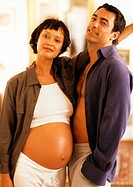 Pregnant woman standing with man, looking at camera, portrait