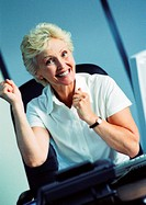 Businesswoman raising fists and smiling, portrait (thumbnail)