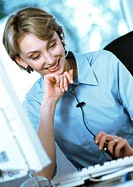 Businesswoman wearing headset at desk (thumbnail)