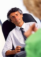 Businessman at desk, listening to woman in blurred foreground