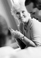 Mature businesswoman in conference, smiling, with two colleagues, B&W