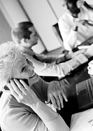 Businesswoman using cell phone in conference room, colleagues in blurred background, B&W