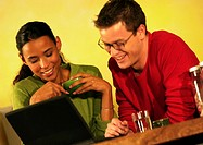 Man and woman with laptop computer, smiling