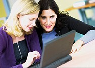 Two women using laptop computer