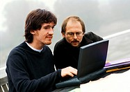Two men working on laptop computer outdoors
