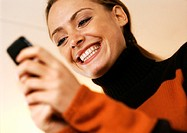 Woman smiling with cell phone in hands, low angle view