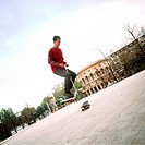 Young man in mid-air with push scooter