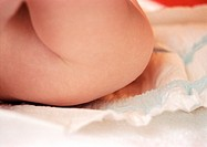 Baby having diaper changed, mid-section, side view, close-up