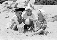 Two girls and boy playing in sand