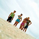 Teenagers in bathing suits standing on sand, low angle view