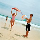 Teenage boy holding beach ball, girl holding kite at the beach
