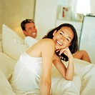 Man and woman on bed, smiling