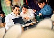 Three men sitting at cafe terrace, looking at documents