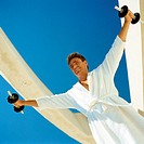 Man lifting weights in bathrobe, low angle view
