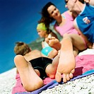 Couple and children lying on beach, focus on child´s feet
