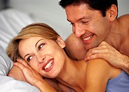 Couple in bed, smiling, close-up