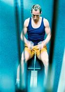 Man using rowing machine, high angle view