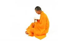 Buddhist monk sitting, side view