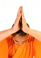 Buddhist monk meditating with hands together over head