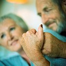 Mature couple holding hands, focus on hands