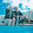 Mature couple sitting on edge of swimming pool, woman splashing water into air