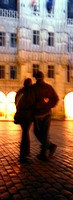 Couple walking with arms around each other at night, rear view, blurred