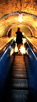Woman riding escalator at night, rear view