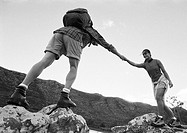 Man helping woman across rocks, low angle view, b&w