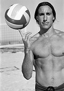 Young bare-chested man, holding volleyball on finger, portait, b&w