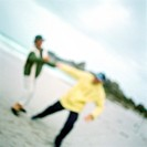 Mature couple playing on beach, blurred