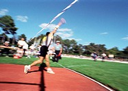Male athlete throwing javelin, blurred motion
