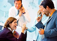 Three business people laughing in office, businessman in background covering mouthpiece of phone