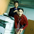 Man and woman standing with guilty expressions near photocopier