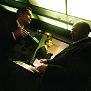 In elevator, businessman holding briefcase full of money out for second businessman