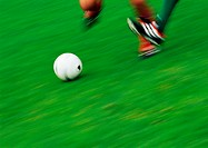 Feet of two soccer players running for ball, low section, blurred