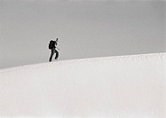 Man hiking across dune, side view, b&w