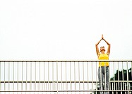 Woman standing on bridge, hands over head, low angle view