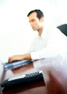 Cell phone on businessman´s desk, blurred background