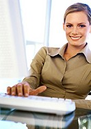 Businesswoman with hand on keyboard, smiling, portrait