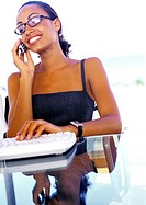 Businesswoman using cell phone and computer