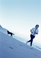 Mature woman running on beach, dog in background