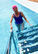 Mature woman in swimming pool, walking up ladder, blurred