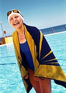 Mature woman with towel around shoulders in front of swimming pool, portrait