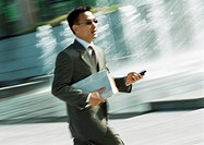 Businessman walking with cell phone in hand, three quarter length, tilt