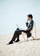 Businessman sitting on beach with laptop on knees, full length, close-up, blurred